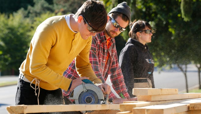Michael Koch, left, and Jared Camp trim lumber as they help to frame a new Habitat for Humanity house under construction Wednesday, September 30, 2015, at 628 N. 18th Street in Lafayette. Both are from The Crossing, a faith-based alternative school at 215 Smith Street in Lafayette.