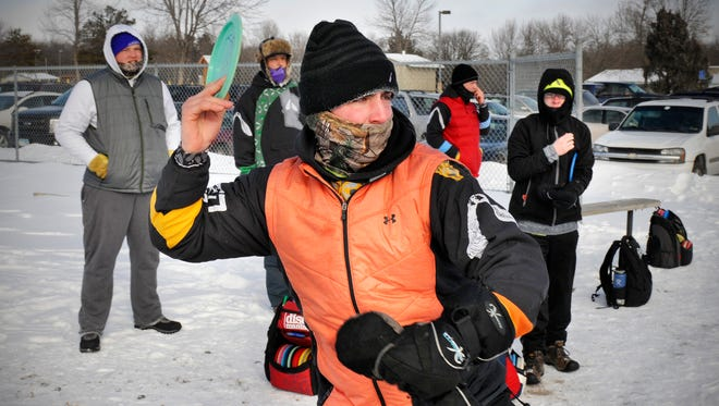 Bundled-up participants take their shots from a tee box during the 2016 Ice Bowl on Saturday at the Millstream Disc Golf Course in St. Joseph.