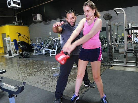 Trainer Gabino Gonzalez guides Dima Azzam through a workout at the Metamorphosis Gym. Azzam is battling a lung illness, but continues to exercise and stay positive.