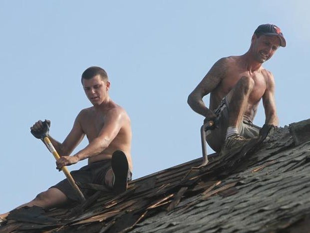 Noah Miner, left, and Robert Mendenhall work on replacing a roof on a home on Ridgeway Avenue in Rochester on Wednesday.