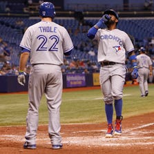 Blue Jays shortstop Jose Reyes  reacts at home plate after he hit a 3-run home run  against the  Rays at Tropicana Field.