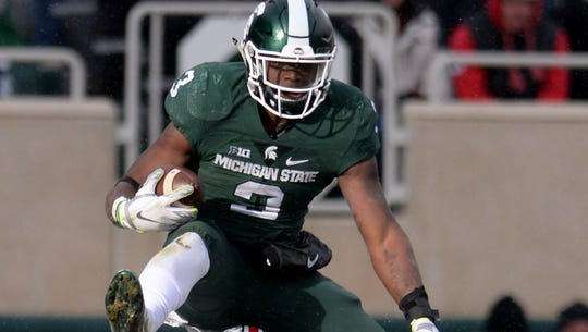 Sophomore running back LJ Scott leaps over Ohio State