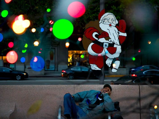 Homeless man Alonzo Harrison, 47, takes a nap on a bench at Pershing Square decorated with Christmas lights in the background on Monday, Dec. 4, 2017, in Los Angeles.