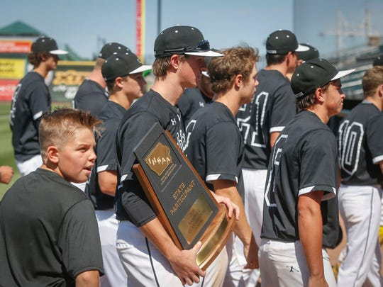 Members of the Johnston baseball team carry the state participation trophy off the field after a 7-5 loss to Cedar Rapids Washington in Class 4A action during the Iowa high school boys state baseball tournament on Wednesday, July 25, 2018, in Des Moines.