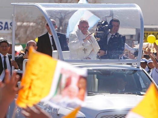 El Papa Francisco da su bendición arriba del papa móvil.