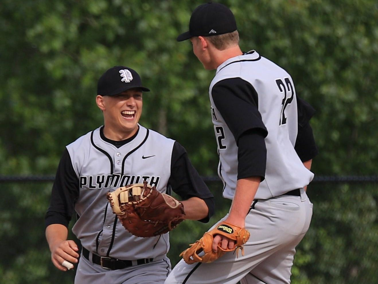 Plymouth seniors Seth Hubbard (left) and Kevin Anthony (No. 32) celebrate after first baseman Hubbard makes the final out in the Wildcats' 2-1 win over Westland John Glenn Monday. The victory gave Plymouth its first baseball district championship.