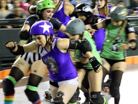 A Jammer with the roller derby name of Rose-Ty Her 9th of Las Catrinas powers her way through the pack during their bout against Las Viudas Negras Sunday night in the County Coliseum. Las Viudas Negras prevailed 59-36.