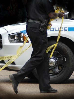 A Jackson police officer works a crime scene.