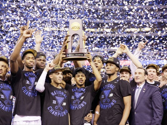 Duke players celebrate with the trophy after their 68-63 victory over Wisconsin in the NCAA Final Four college basketball tournament championship game Monday, April 6, 2015, in Indianapolis.