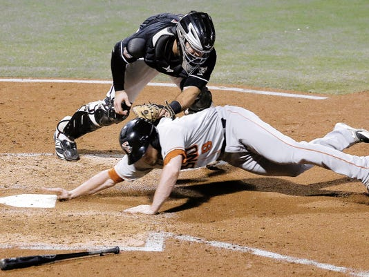 MARK LAMBIE—EL PASO TIMES  Chihuahuas' catcher Jason Hagerty tags out Fresno's Tyler Heineman at home plate during game 4 of their PCL division championship Saturday at Southwest University Park.