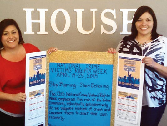 Submitted Photo   Julie Flores, left, and Irene Trejo of the Healing House studied the poster board created by the advocates for National Crime Victims' Right Week. The Healing House is Luna County's shelter for survivors of domestic violence.