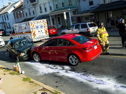 Emergency crews work at the scene of a two-vehicle accident on Maple Street near Seventh Street on Tuesday at 5:43 p.m.