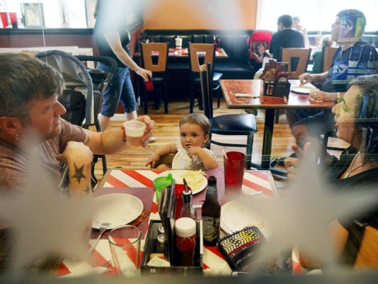 Cliff Martin and Karen Gonano-Martin of Delta eat lunch with their 18-month-old daughter Matilda Martin during Delta Pizza's grand reopening celebration Saturday in Delta. After a fire severely damaged the restaurant in Oct. 2013, owner Sal Ferranti restyled it to be more of a family restaurant and sports bar and had a soft opening in May 2015.