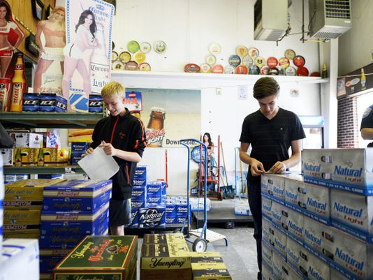 Lance Fries, 14, left, and  Matthew Gauker, 16, place stickers on cases of beer at Golden Brew Distributors in Manchester Tuesday. Northeastern High School SADD members posted stickers advising parents not to serve alcohol to minors in advance of the school's homecoming dance, which is on Saturday.