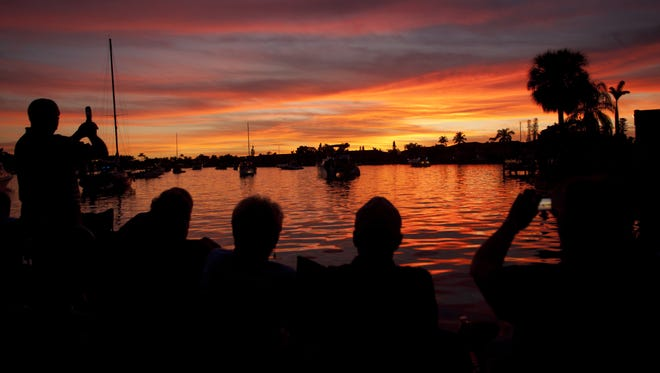 Spectators take photos of the stunning sunset at Bimini Basin at Four Freedoms Park in Cape Coral Sunday 12-16-12 before the start of the annual Holida Boat-A-long.