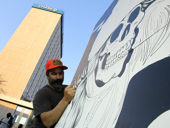 Artist Tocayo works on a painting Saturday at the Neon