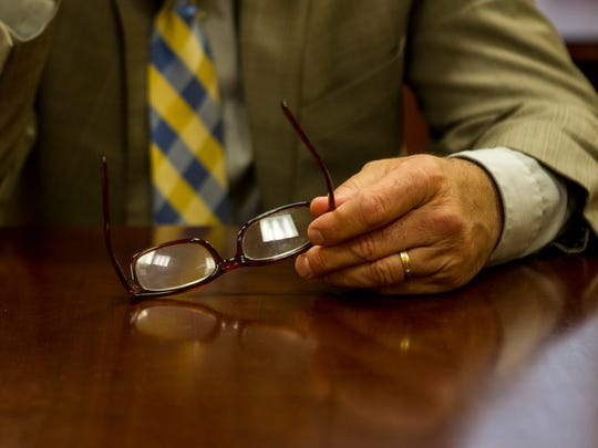 Principal Jeff Brokamp holds his glasses Friday, May 12, 2017 in his office at Walnut Hills High School.