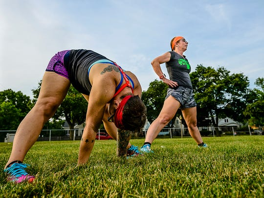 Anna Kaschner ,left, and Tina Stewart stretch Thursday