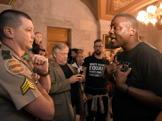 Activist Evan Bunch argues with a Tennessee State trooper asking permission to enter Gov. Bill Haslam's office during a protest which was condemning the display to the bust of Nathan Bedford Forrest displayed at state Capitol.