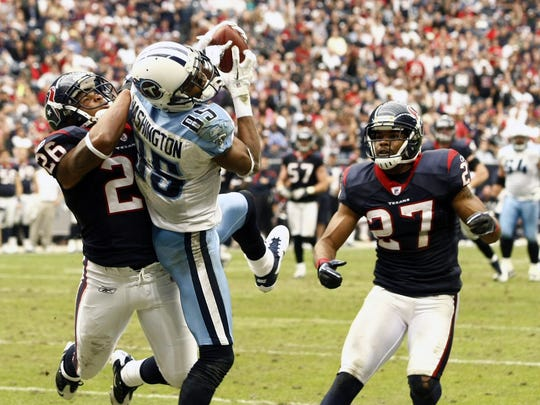 Titans wide receiver Nate Washington scores against Texans defensive back Brandon Harris, left, and defensive back Quintin Demps in the second half Jan. 1, 2012.