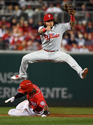 Philadelphia Phillies shortstop Freddy Galvis forces out Washington Nationals center fielder Michael Taylor and throws to first to complete a double play at Nationals Park.