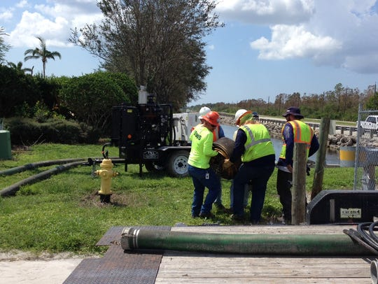 Workers install temporary pumps at a drainage ditch