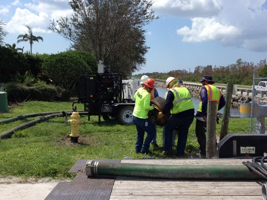 Workers install temporary pumps at a drainage ditch along Bonita Beach Road to help alleviate flooding in Bonita Springs.