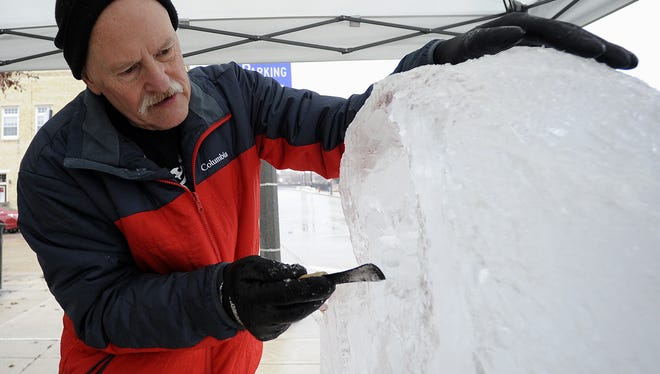 Ice sculptor Jeff Olson, of Egg Harbor, carves a maritime portrait into a block of ice along Eighth Street during the 2015 Ice on 8th event.