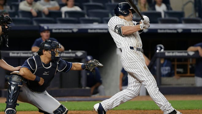 Jacoby Ellsbury follows through on a two-run double as Tampa Bay Rays catcher Hank Conger (24) watches during the eighth inning on Friday, April 22, 2016.