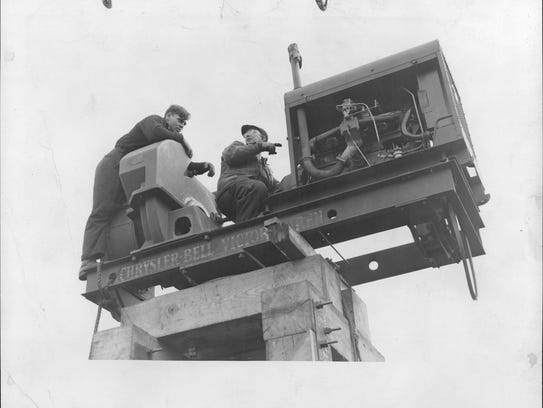 "Workmen are shown astride the ""SCREAMING MAMIE"", a"