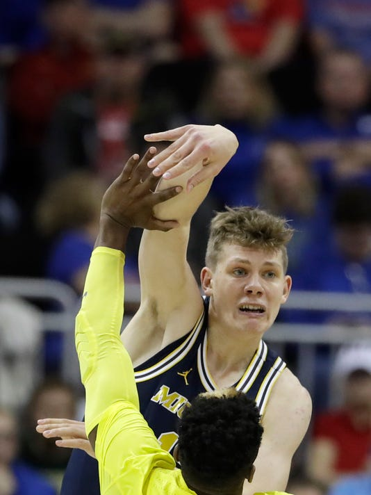 Michigan forward Moritz Wagner passes the ball over Oregon guard Dylan Ennis (31) during the second half of a regional semifinal of the NCAA men's college basketball tournament, Thursday, March 23, 2017, in Kansas City, Mo. (AP Photo/Charlie Riedel)