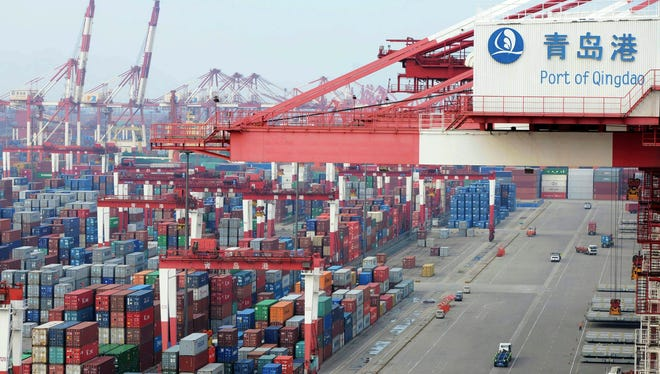 Trucks pass through a container port in Qingdao in east China's Shandong province.