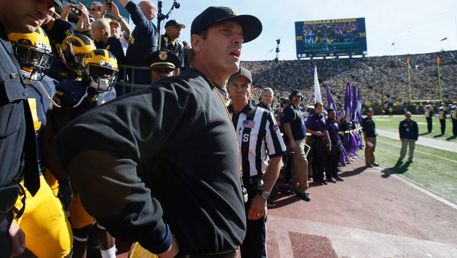 Michigan football coach Jim Harbaugh comes out of the tunnel before a game against Northwestern on Oct. 10, 2015.