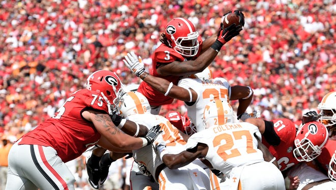 Georgia Bulldogs running back Todd Gurley (3) scores a touchdown over the Tennessee Volunteers defense during the first half at Sanford Stadium.