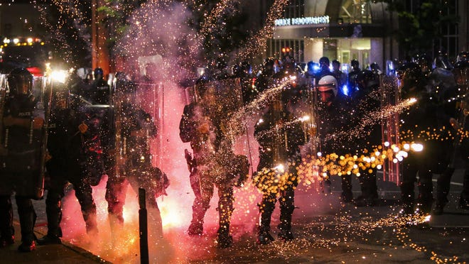 Fireworks explode as officers clash with protesters in front of police headquarters in downtown St. Louis on Monday.