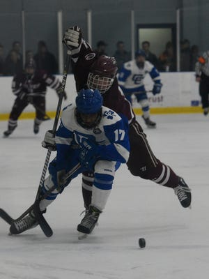 Catholic Central's Ryan Clemons (17) is taken down at the blue line by Culver's Brennan Coulson.