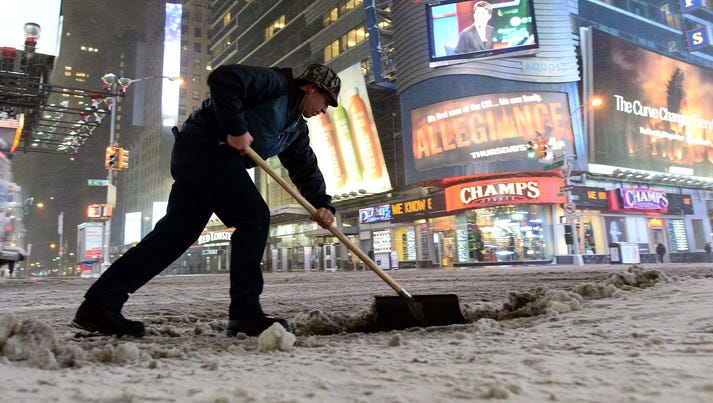 A man shovels snow from a deserted street in New York's