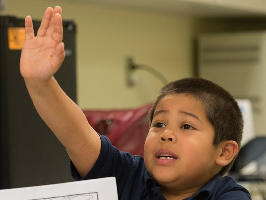 Kindergartener Randy Osorio-Valdez raises his had to answer a question in his ESOL class at Prince Street Elementary School.