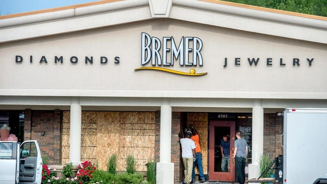A City of Peoria crew boards up windows Monday, June 1, 2020 at Bremer Jewelry, 4707 N. University St., after looters allegedly broke in to the store overnight.