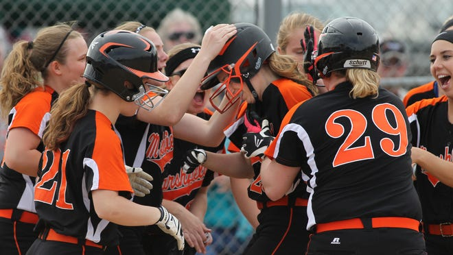 Marshfield's Emily Draeger, center, is mobbed by teammates at home plate after she belted a two-run home run Tuesday against Wausau East at Lee Field in Marshfield.