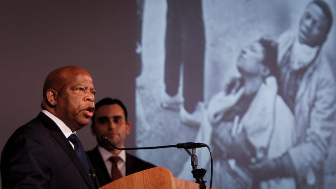 """Congressman John Lewis, co-author of """"March Book One,"""" speaks Monday at the Hannah Community Center in East Lansing. Flanking him is co-author Andrew Aydin."""