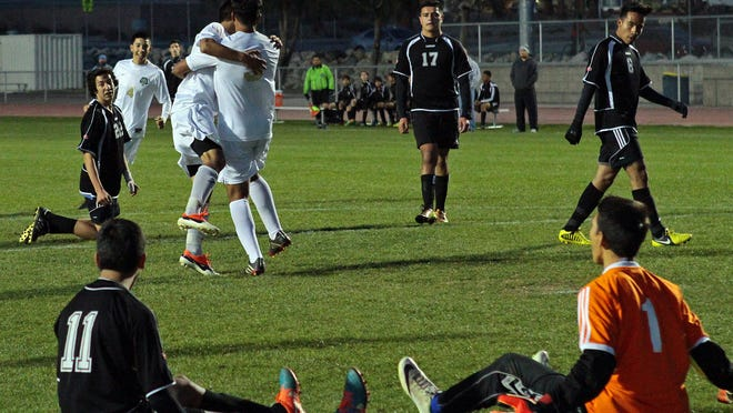 Desert Hot Springs player Carlos Minero (9, white, right) gets a hug from a teammate in excitement after scoring on Yucca Valley (black uniforms) in the first half of a boys soccer game on Tuesday, January 13, 2015 in Desert Hot Springs.