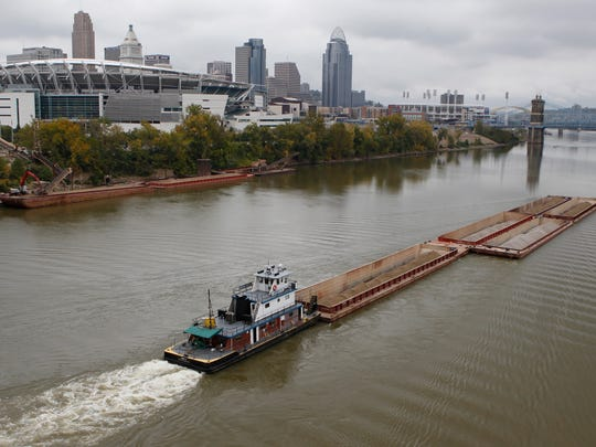 A barge moves freight on the Ohio River near downtown Cincinnati.