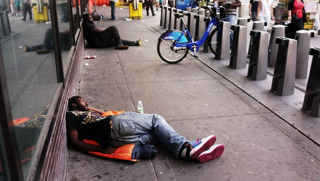 A man sleeps on the ground outside the Port Authority Bus Terminal on Aug. 21 in New York City.