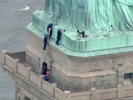 This still image taken from video Courtesy of PIX11 News in New York, shows police talking to a woman who climbed to the base of the Statue of Liberty in New York on July 4, 2018.  According to media reports, Liberty Island has been evacuated and ferries to the site have been halted, while law enforcement attempt to get the woman down from the statue.