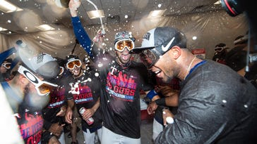 The Rangers celebrate their AL West-clinching win over the Angels on Sunday inside their locker room at Globe Life Park.