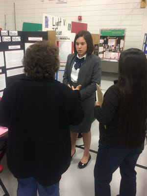 A student presents her science fair project to judges during the Farmington Municipal School District Science Fair at Hermosa Middle School on Saturday.