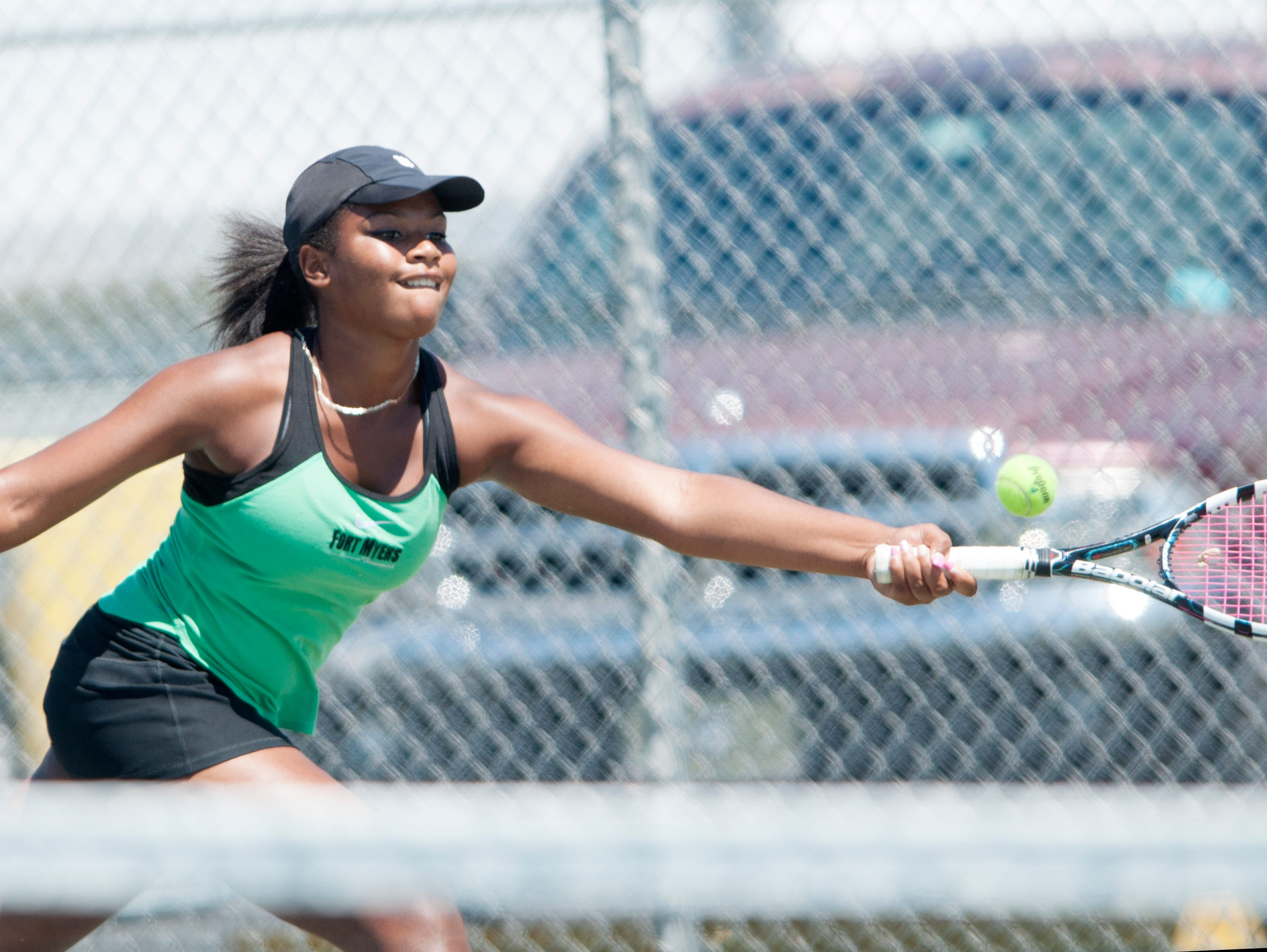 Shani Idlette, of the Fort Myers High School tennis team, makes a return while competing against Barron Collier's Amand Ruci during the Region 3A-3 girls tennis regional semifinal on Tuesday.
