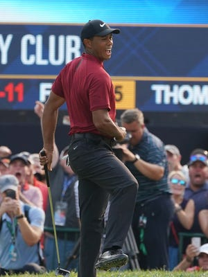 Tiger Woods celebrates after making a birdie putt on the 18th green during the final round of the PGA Championship.