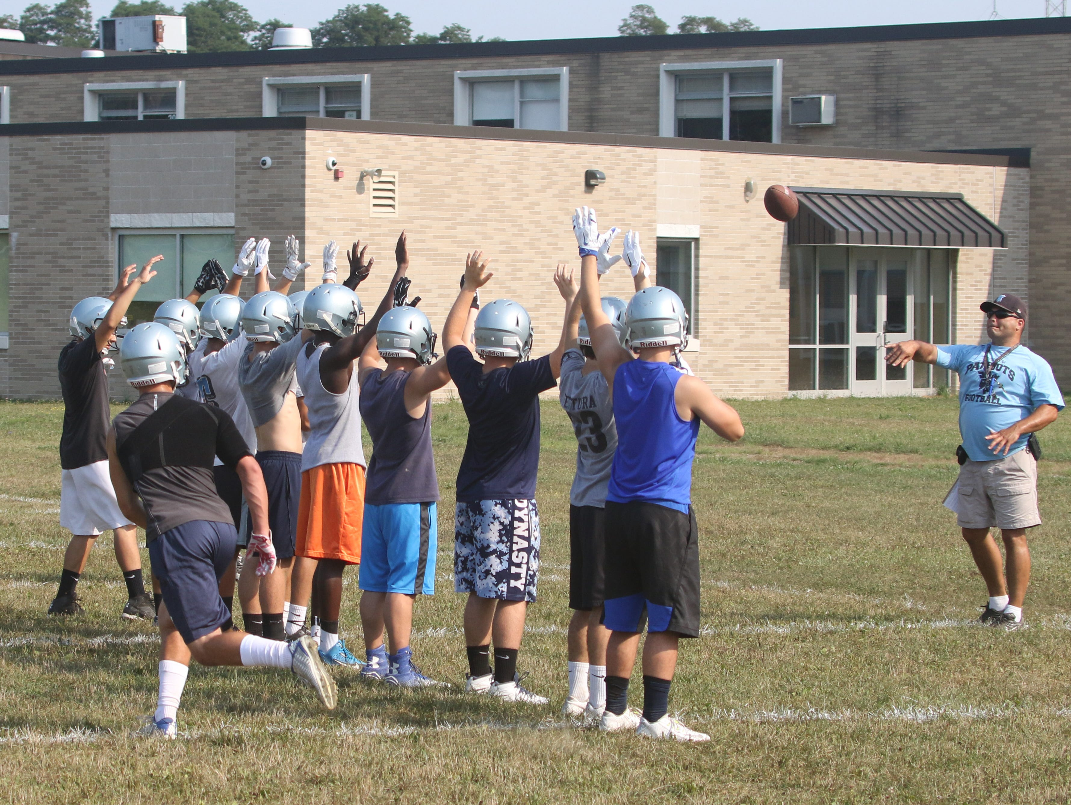 John Jay High School football special teams coach TBob Schumacher throws a ball during a drill at practice on Wednesday.